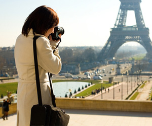 A tourist taking a photo of the Eiffel Tower
